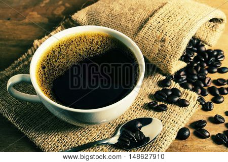 Vintage coffee cup with coffee bean on brown wooden table in still life and dark filter color tone