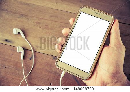 Hand man holding smartphone mobile white screen with earphone on old wood desk vintage style