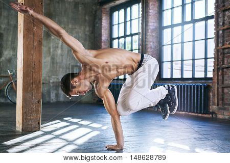 Young man break dancing in old sunny urban interior