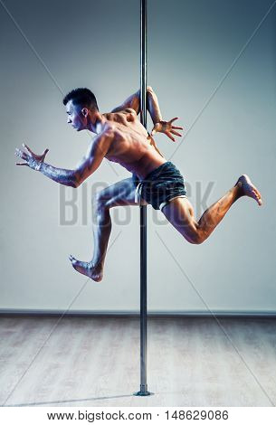 Young strong pole dancing man in running pose. Warm and cold colors effect.