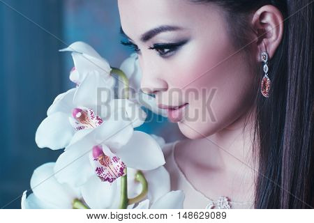 Young asian woman with orchid flower portrait close-up. Focus on lips.