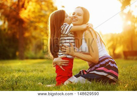 Daughter kiss her mother on the cheek. Family sits on a green lawn in the city park outdoors.