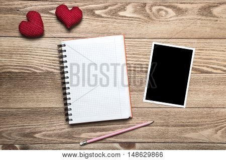 Blank photo frame and love hearts on wooden table