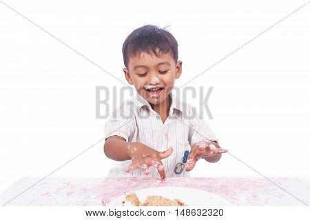 little boy happy play cream cake on white background