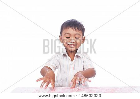 little boy happy play cream cake on white backgrond