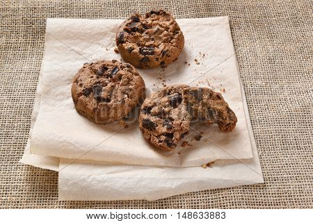 Closeup of a pile of chocolate chocolate chunk chip cookies on parchment paper and burlap.