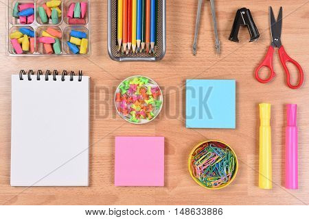 Colorful Back to School Supplies arranged on a wood desk top.