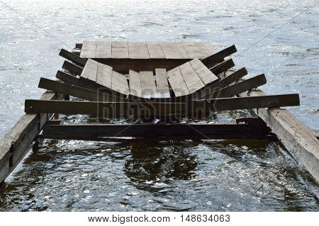 Broken wooden dock in the waves of the river