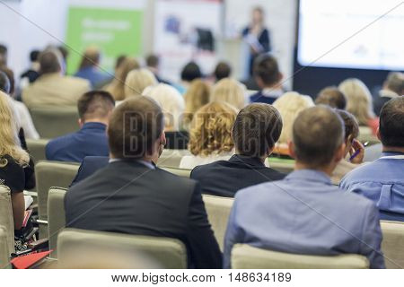 Professional Female Host Speaking in Front of the Large Audience During Business Conference. Horizontal Shot