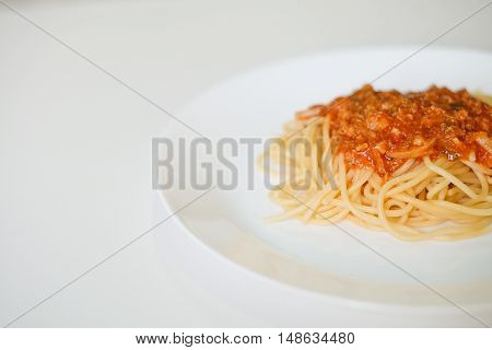 Italian spaghetti topped with a tasty tomato and  beef sauce on white table