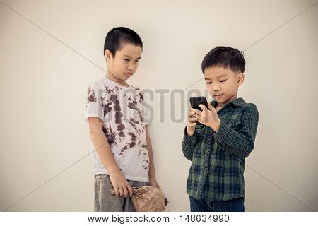 Young Boy Play Smartphone Compare With Poor Boy