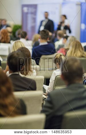 Business Ideas and Concepts. People at the Business Conference Listening to Hosts in Front of the Stage. Vertical Image Orientation