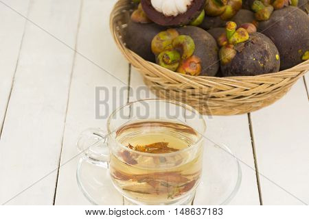 Mangosteen juice from herbs and mangoteen  in the basket on wooden white background.Top view and zoom in.