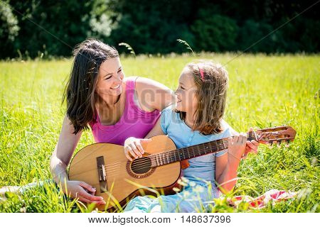 Mother teaches plaing guitar her child - outdoor in nature on sunny day