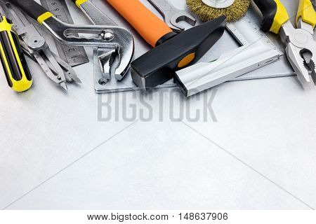 Tool Set Of Hammer, Rulers, Wrench And Pliers On Scratched Metal Background