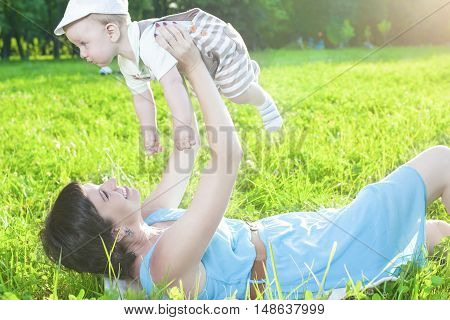 Family Life Concepts. Portrait of Mother with Her Toddler Son Playing Outdoor in Park. Horizontal Image Orientation