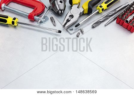 Drills, Screwdrivers, Clamp, Pliers And Other Hand Tools On Scratched Metal Plate Background