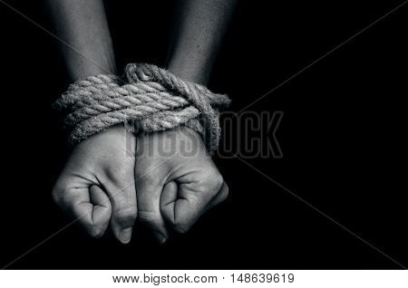 Hands of a missing kidnapped, abused, hostage, victim woman tied up with rope in emotional stress and pain, afraid, restricted, trapped, call for help, struggle, terrified, locked in a cage cell.