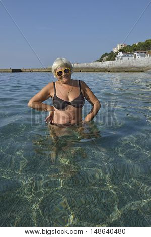 Aged Lady Is Standing In Transparent Water Of Sea Beach.