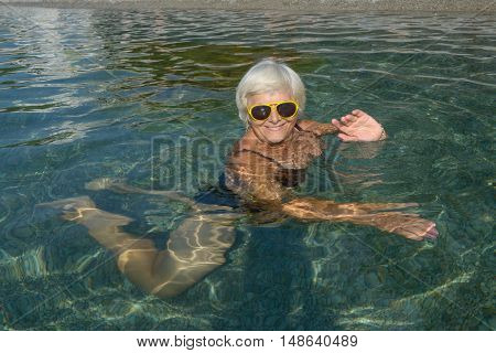 Aged Lady Is Lying In Clear Transparent Water Sea Beach.