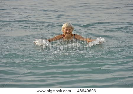 Aged Woman Is Doing Motions In Light Clear Sea Water.