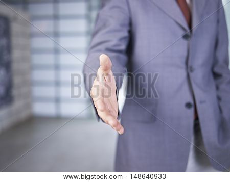 businessman/real estate agent reaching out for handshake.
