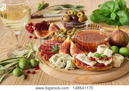 Delicious appetizer ham, roquefort, feta cheese, figs, fig jam, olives, pomegranate, wheat rusks ready to eat with ham, feta and with roquefort, olives served on light wood board, glass of white wine.