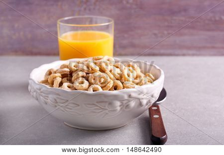 Breakfast cereal hoops in a bowl and glass of orange juice