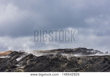 Geothermal landscape Krafla on Iceland with black ground lava and steam.
