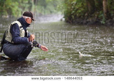 Fly-fisherman catching trout in river, under the rain