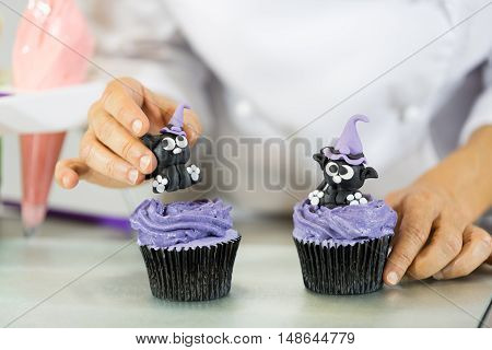 Confectioner decorate some cupcakes in the kitchen