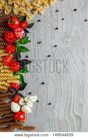 Mixed Of Two Colored Pasta Near Tomatoes, Garlic And Basil On Grey Wooden  Background. Raw  Frame. C