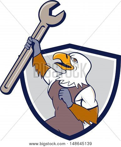 Illustration of a mechanic american bald eagle holding spanner looking to the side set inside shield crest on isolated background done in cartoon style.