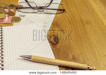 Spiral notebook and pen on wooden desk - Office desk with an opened graphic notebook a pen some euro coins bills and a pair of glasses