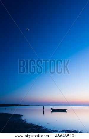 Mystical sea with boat. Abstract natural backgrounds. Moon scene after sunset