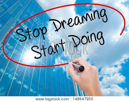 Man Hand Writing Stop Dreaming Start Doing  With Black Marker On Visual Screen