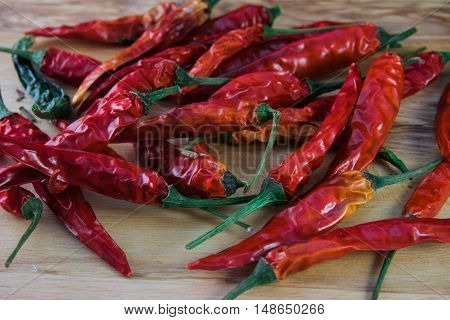 a lot of different chilli pepper lying on the wooden background