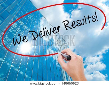 Man Hand Writing We Deliver Results! With Black Marker On Visual Screen