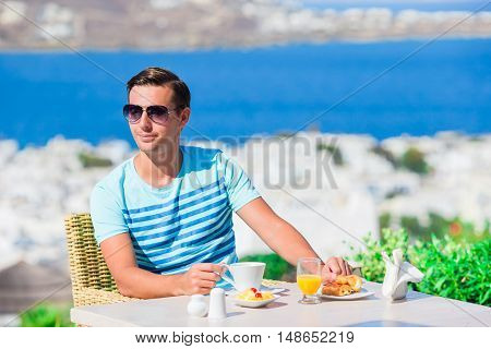 man having breakfast at outdoor cafe with amazing view on Mykonos town.