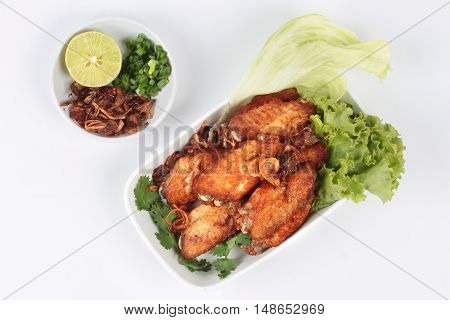 Deep fried chicken topped fried sliced red onion served with side dish as halve green lemon ,minced shallots and filled fried red onion on white