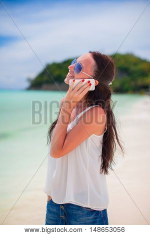 Close-up young beautiful woman at the beach talking on her phone