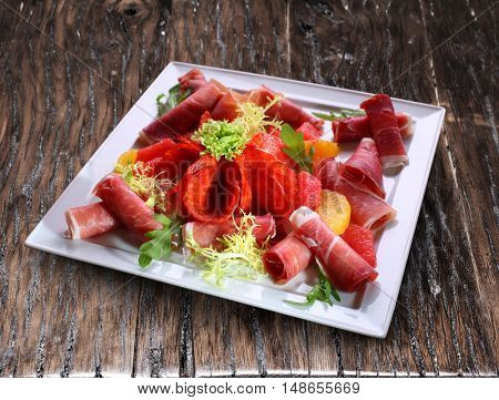 Meat platter or cold cut platter on the wooden table.