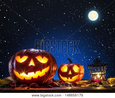 Grinning pumpkin lantern or jack-o'-lantern is one of the symbols of Halloween. Halloween attribute. Night sky background.