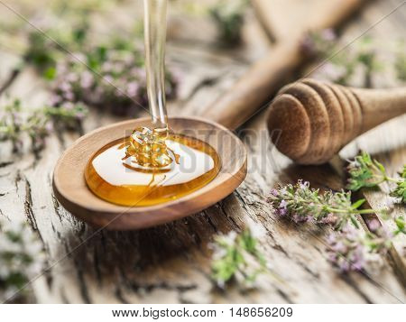 Herbal honey pouring into the wooden spoon. Spoon is on old wooden table surrounded with levender flowers.