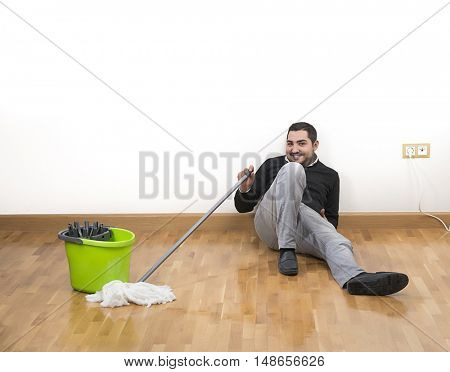 Adult man tired of mopping the floor resting with space for your text.