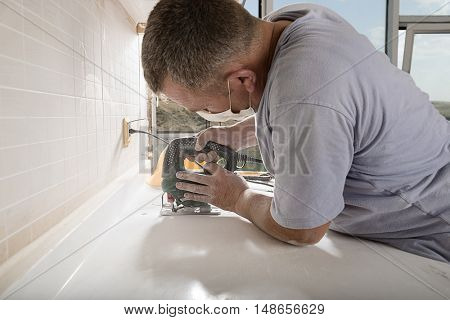 Manual worker cutting kitchen countertop with electric saw close up.