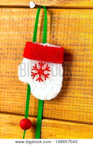 Toy red Christmas mitten with snowflakes on a nail on a background of wooden boards