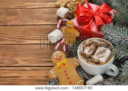 Hot chocolate and Christmas gingerbread men on a brown background