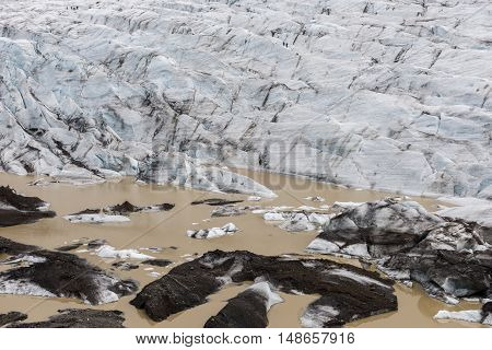 Skaftafellsjokull Glacier with brown lake at the bottom of the glacier with ice blocks on Iceland.