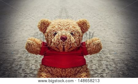 Lonely teddy bear on the road vintage style